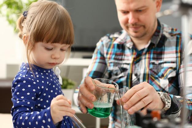 Homem e menina brincam com líquidos coloridos