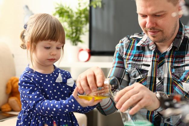 Homem e menina brincam com retrato de líquidos coloridos.
