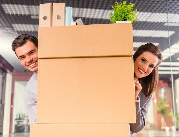 Homem e menina em pé atrás da caixa e sorrindo.