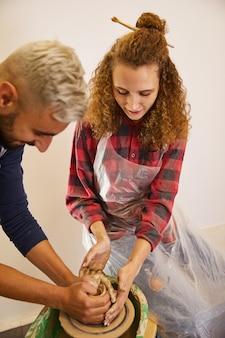 Homem e menina encaracolada estão moldando um vaso