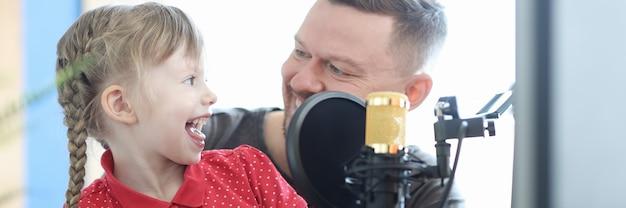Homem e menina estão gravando música no microfone. conceito de aulas de treinamento de voz infantil