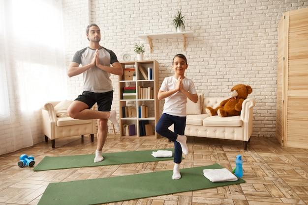 Homem e menina estão tendo o treinamento de fitness em casa.