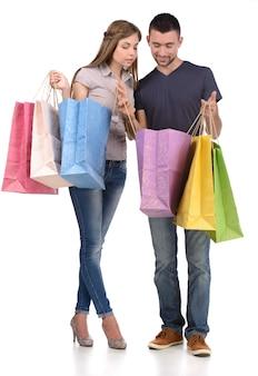 Homem e menina segurar sacos de compras nas mãos.