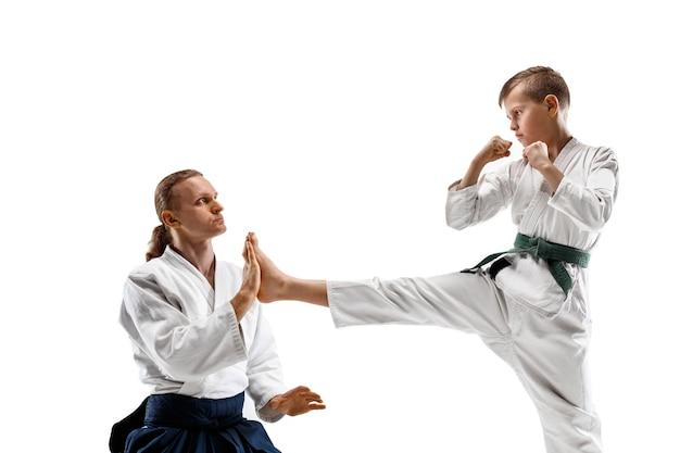 Homem e menino adolescente lutando em um treinamento de aikido na escola de artes marciais