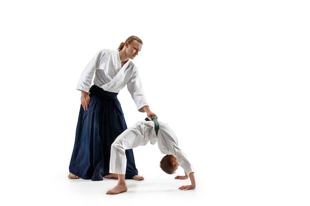 Homem e menino adolescente lutando no treinamento de aikido na escola de artes marciais