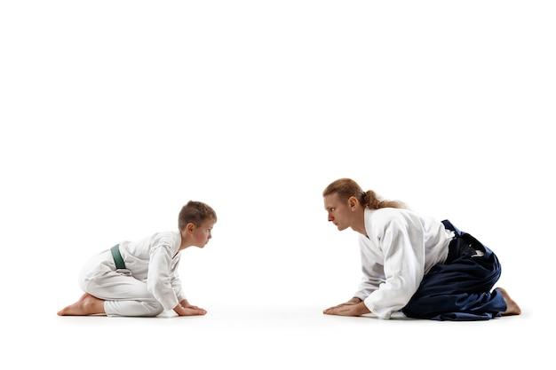Homem e menino adolescente treinando aikido na escola de artes marciais