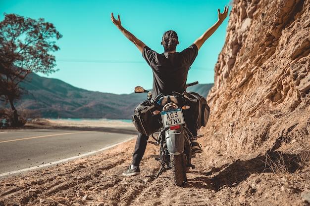 Homem e moto nas montanhas