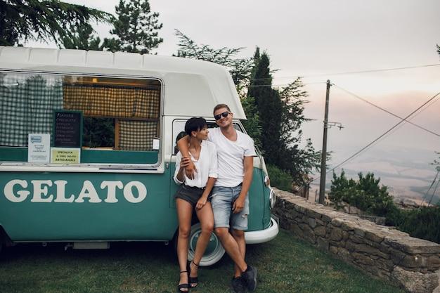 Homem e mulher abraçam e sorriem sentados em um antigo ônibus