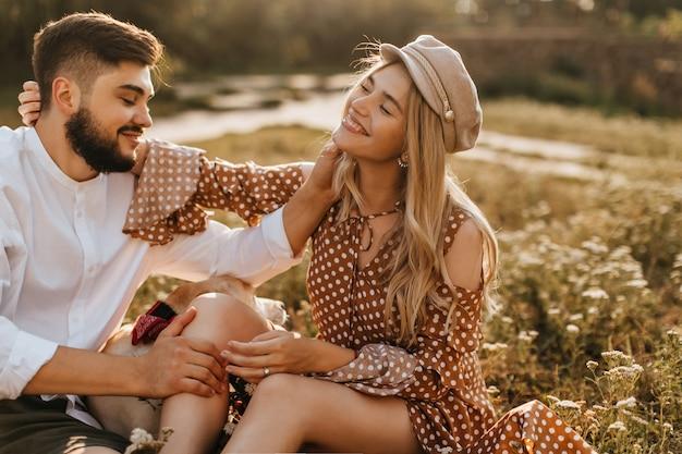 Homem e mulher acariciam suavemente um ao outro enquanto estão sentados na grama. casal romântico sorrindo poses com labrador.