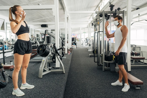Homem e mulher acenando um para o outro na academia