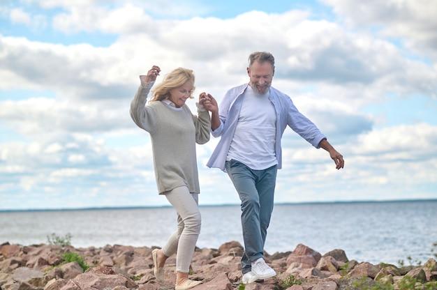 Homem e mulher adultos caminhando na praia