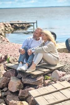 Homem e mulher adultos descansando à beira-mar