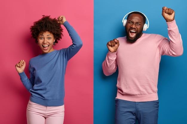 Homem e mulher afro-americana alegre carismática levantam as mãos e dançam alegremente com o ritmo da música, usam fones de ouvido, posam contra o espaço azul e rosa. pessoas