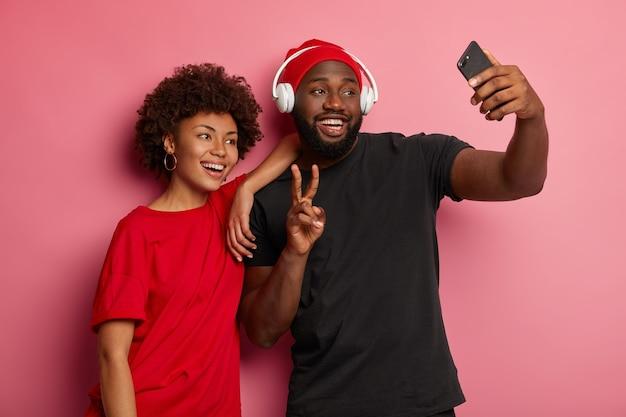 Homem e mulher afro-americanos tirando uma selfie em um gadget moderno, fazendo gestos de paz e sorrindo alegremente para a câmera