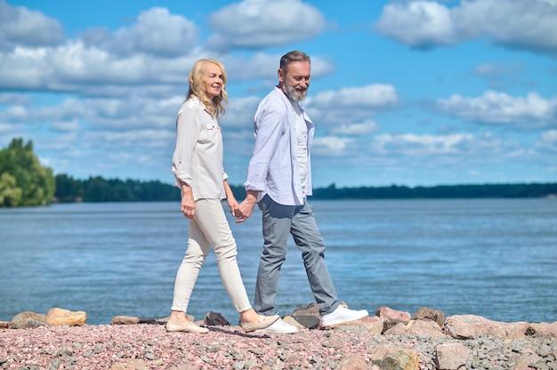 Homem e mulher alegres caminhando à beira-mar