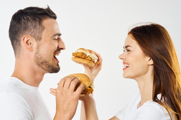Homem e mulher alegres com hambúrgueres e lanches rápidos divertidos