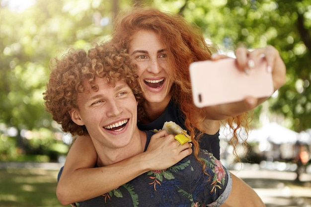 Homem e mulher alegres descansando ao ar livre tirando selfies