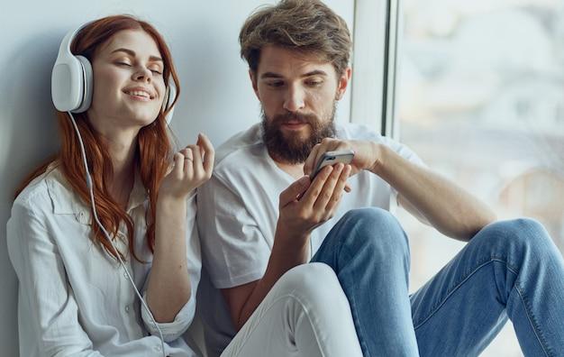 Homem e mulher alegres ouvindo música em casa perto do descanso da janela