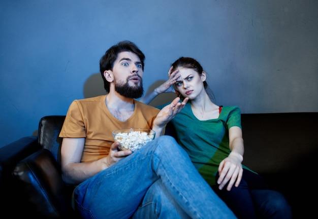 Homem e mulher alegres sentados no sofá assistindo filmes pipoca de férias em família