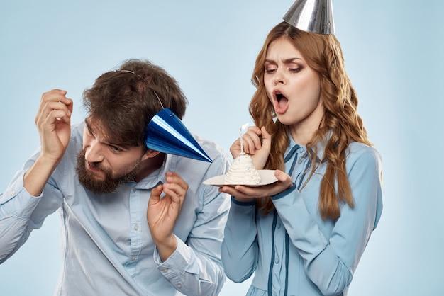Homem e mulher alegres soprando velas de bolo decoração de férias fundo azul