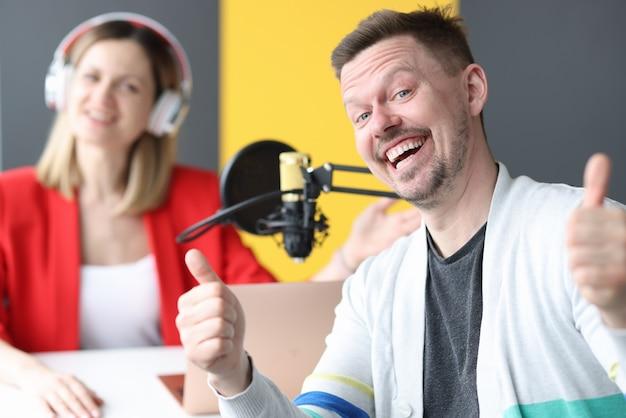 Homem e mulher alegres trabalhando no ar da estação de rádio