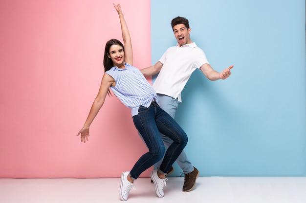 Homem e mulher animados em trajes casuais rindo e se divertindo juntos, isolados sobre uma parede colorida