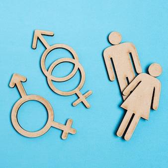 Homem e mulher ao lado de sinais de gênero