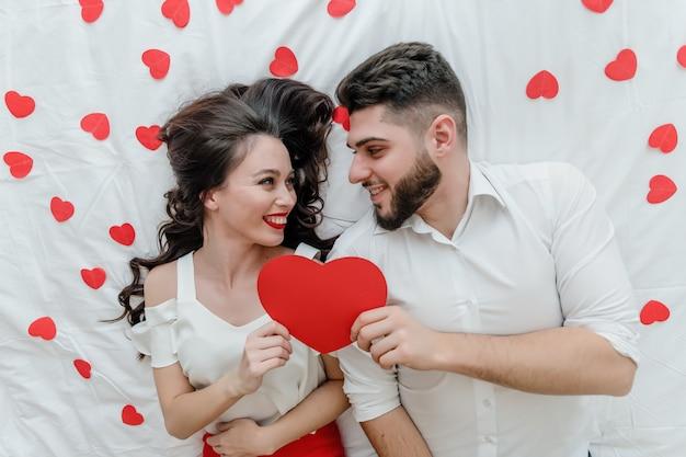 Homem e mulher apaixonada na cama com coração vermelho em forma de cartão de dia dos namorados em casa