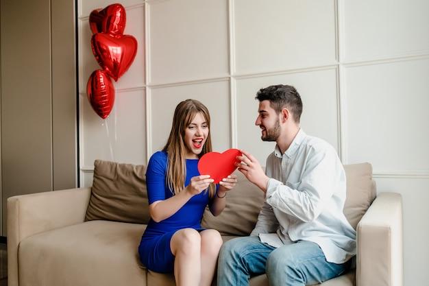 Homem e mulher apaixonada por coração vermelho em forma de cartão e balões de dia dos namorados