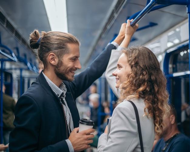 Homem e mulher apaixonados olhando um para o outro em um trem do metrô