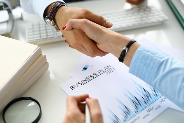 Homem e mulher apertam as mãos plano de negócios 2021.