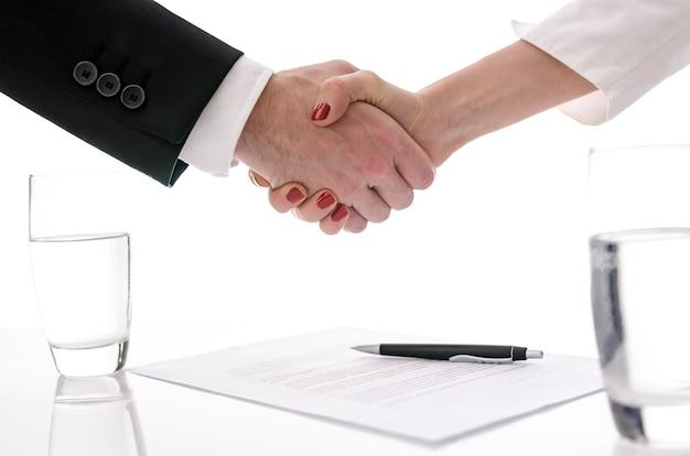 Homem e mulher apertando as mãos acima da mesa com contrato assinado.