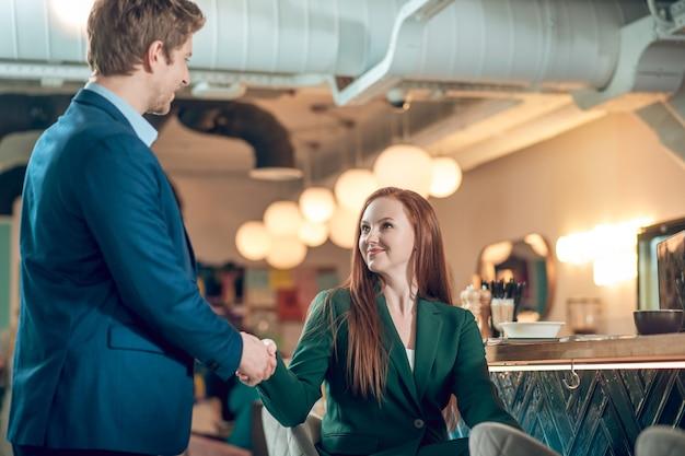 Homem e mulher apertando as mãos em um café