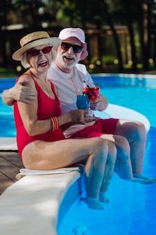 Homem e mulher aposentados segurando óculos com coquetel e passando as férias perto da piscina