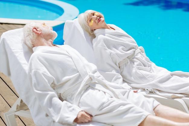 Homem e mulher aposentados vestindo roupões de banho brancos relaxando perto da grande piscina externa