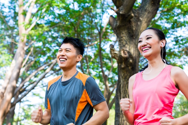 Homem e mulher asiáticos correndo no parque da cidade