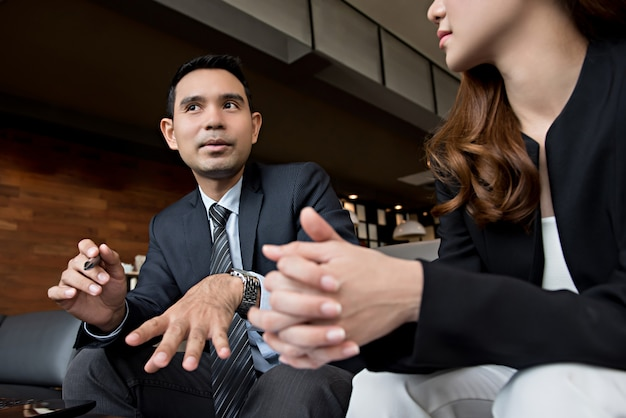 Homem e mulher asiáticos discutindo detalhes de negócios em uma sala de café