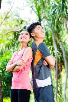 Homem e mulher asiáticos fazem uma pausa após uma corrida esportiva no parque da cidade