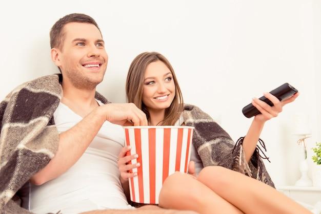 Homem e mulher assistindo filme com pipoca antes de dormir