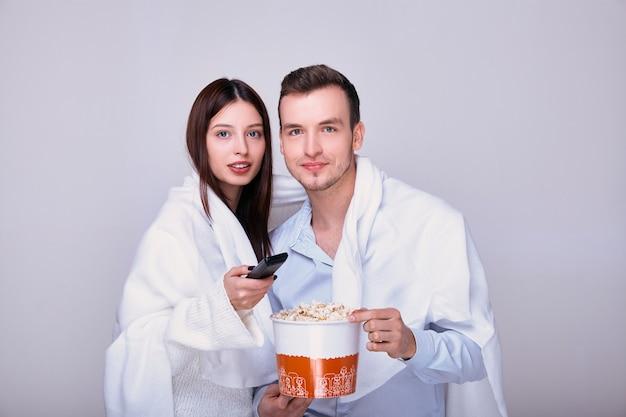 Homem e mulher assistindo tv e comendo lanche de pipoca.