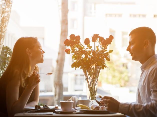 Homem e mulher atraente na mesa com sobremesas e flores