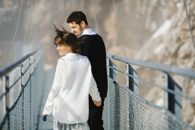Homem e mulher atravessando a ponte juntos