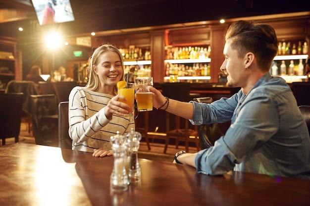 Homem e mulher bebem álcool e conversam à mesa no bar. grupo de pessoas relaxando no bar, estilo de vida noturno, amizade, celebração de evento