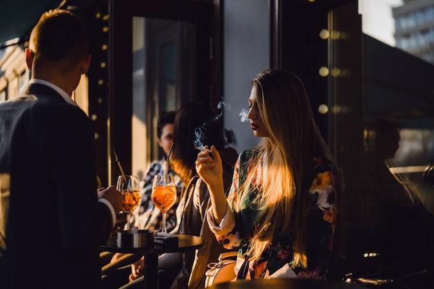 Homem e mulher bebem coquetéis em um café de rua no terraço de verão. elegante casal bebe aperol spritz.