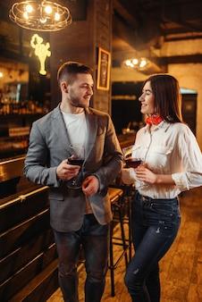 Homem e mulher bebem vinho tinto no balcão do bar