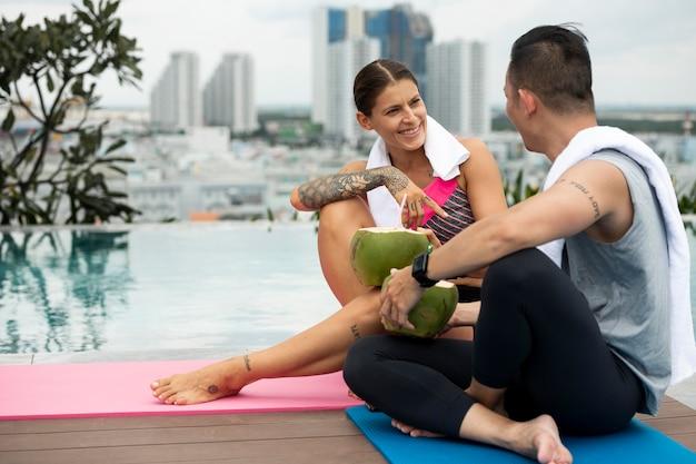 Homem e mulher bebendo água de coco depois da ioga