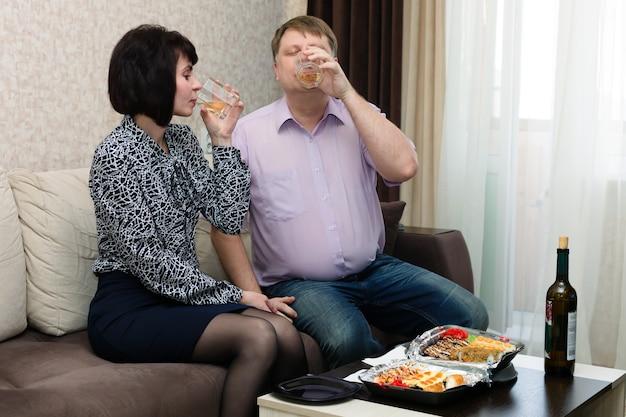 Homem e mulher bebendo vinho no sofá, primeiro encontro