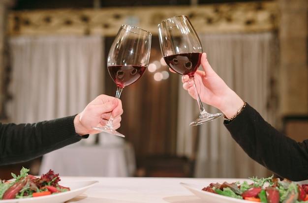 Homem e mulher bebendo vinho tinto. na foto, close-up mãos com óculos.