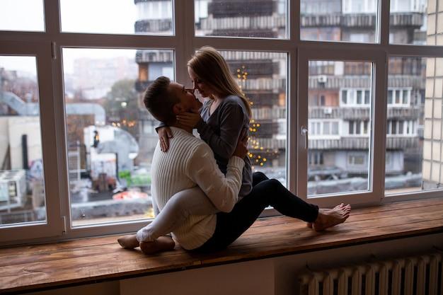 Homem e mulher beijando enquanto está sentado no parapeito da janela em casa. conceito de amor, felicidade, pessoas e diversão.