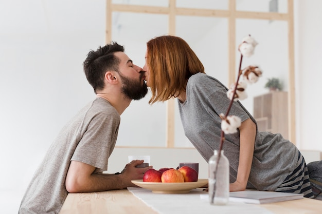 Homem e mulher beijando na cozinha